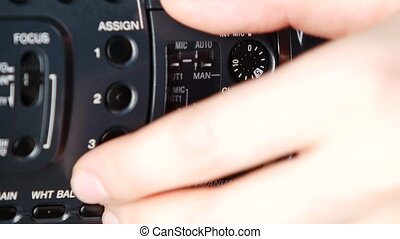Hand opens audio levels video outputs of camera, close up -...