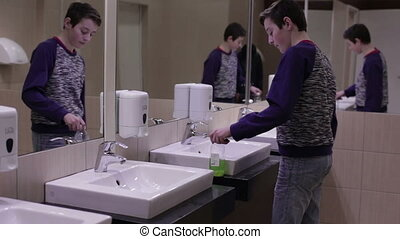 Teen washes his hands in the sink