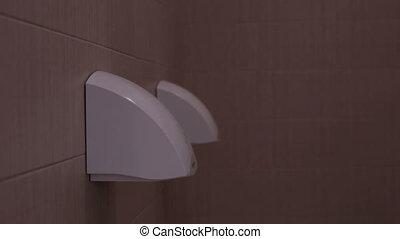 Teen dry hands on hand dryer in toilet