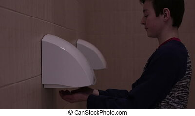 Teen dry hands on hand dryer - Teenager boy dry hands on...