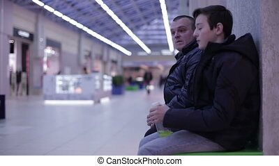 Teenager talking with a man sitting on bench