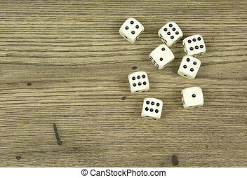 Dice on old,wooden table - Seven white dice scattered on the...