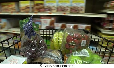 Pushing a shopping cart in a grocery store 3 of 4 - Grocery...