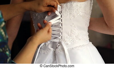 Bride putting on her white wedding dress at wedding day