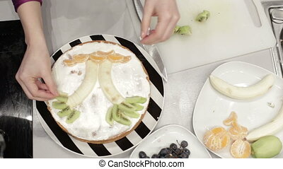 Woman sponge cake decorated with fruits
