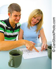 Young Couple Looking At Floor Plan - happy young caucasian...