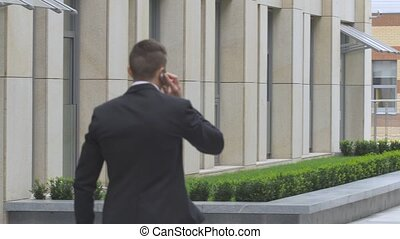 Young man speaking on the phone while walking along modern building