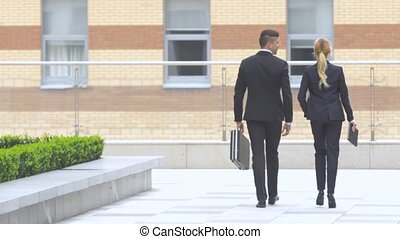 businesspeople walking on the street of an business center -...