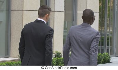 Two businessman walking on the street near office building