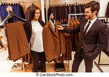 People in suit shop - Young beautiful female shop assistant...