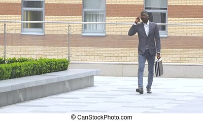 Full length portrait of a happy young man walking and talking on mobile phone
