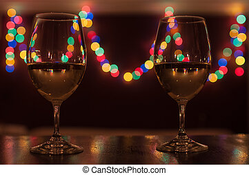 Two glasses of white wine on a romantic candle light dinner