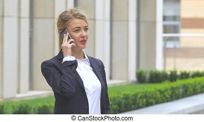 beautiful blonde business woman on the phone at modern building. Close up