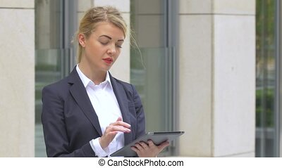 elegant business woman with tablet computer near office...