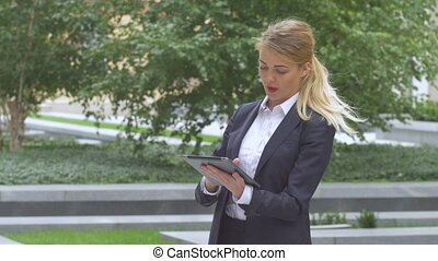 woman with tablet computer near office building close up -...
