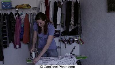 Woman ironing shirt - Woman iron to iron a man's shirt on...