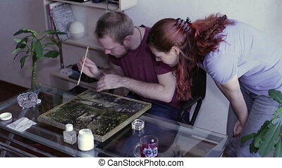 Man and woman painting restored - Man with a brush apply a...