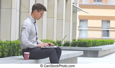 businessman sitting outdoors with laptop