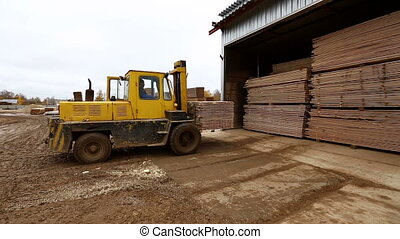 Forklift loading stack of boards at warehouse - View on...