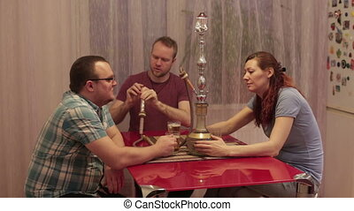 Friends smoking hookah and playing cards - Two men and a...