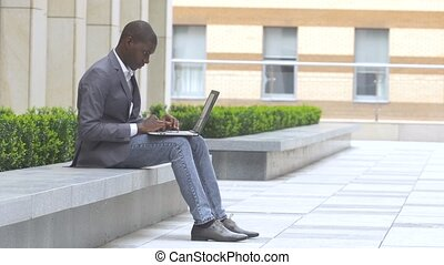 African American guy displaying computer laptop on outdoors...