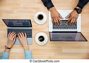Top view of man and woman working with two laptops