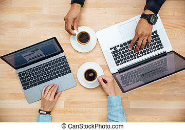 Man and woman with two laptops drinking coffee together -...