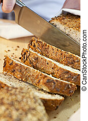 Close up of Slicing Rustic Wholemeal Seeded Loaf of Bread -...