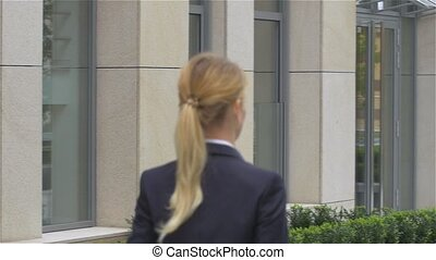 elegant blonde business woman with tablet computer goes...