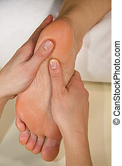 foot reflex zone massage - a closeup of a foot of a natural...