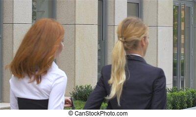 Two businesswoman walking on the street near office...