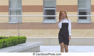 Successful businesswoman talking on cellphone while walking...