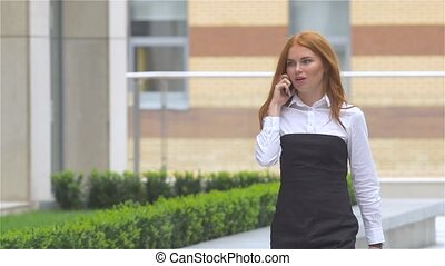 Successful happy businesswoman talking on cellphone while walking outdoor. slow motion