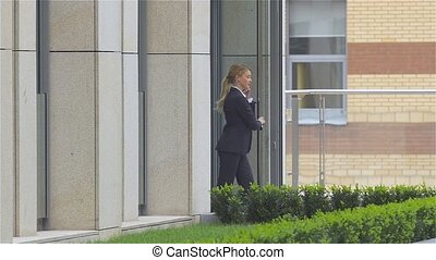 Successful woman talking on cellphone while walking outdoor...