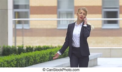Successful blond woman talking on cellphone while walking...
