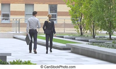 business colleagues walking on the street of an business center. slow motion