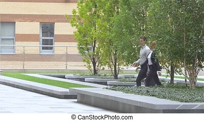 Two business colleagues walking on the street of an business center. slow motion