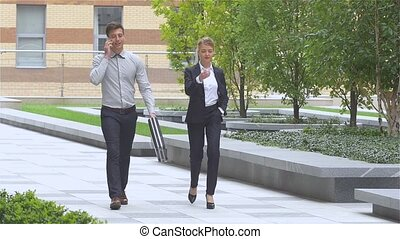 Two successful business colleagues walking on the street of an business center. slow motion