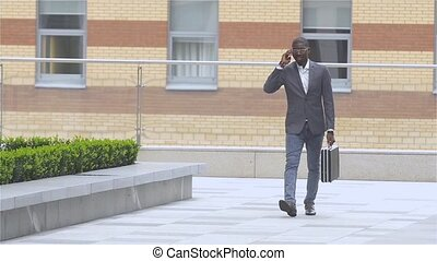 Full length portrait of a happy young man walking and talking on mobile phone, slow motion