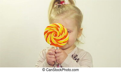 Cute girl chews candy - Little girl eating candy on a stick