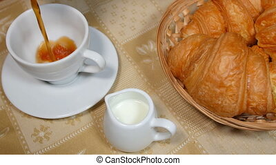 Pouring Coffee into Cup with Croissant