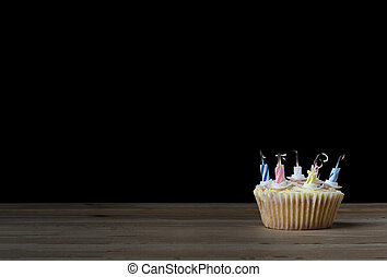 Birthday Cupcake with Candles Blown Out on Black - A...