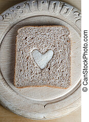 Slice of Brown Bread with White Heart on Vintage Wooden...