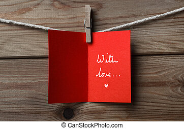 Red Greetings Card Pegged to String on Wood - A red greeting...