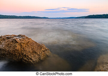 Rocky Shoreline of a lake at sunset - Long exposure of a...