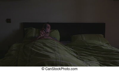 Young man in bed watching TV - Young handsome man in bed...