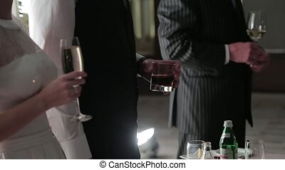 Guests holding glasses with drinks in their hands.