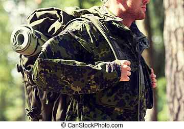 close up of young soldier with backpack in forest - war,...