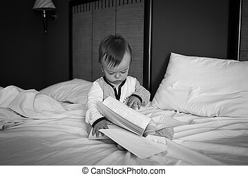 baby sitting on the bed flipping through a book, black and...