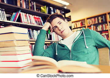 bored student or young man with books in library
